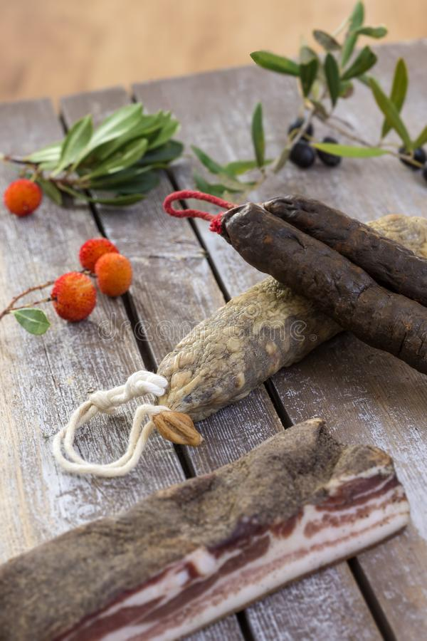 Several variety of traditional Corsican charcuterie with an olive branch and black olives on wooden background and. Several variety of traditional Corsican royalty free stock photography