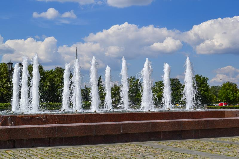 Several vertical jets of the fountain. Decorative fountain in the park area.  royalty free stock image