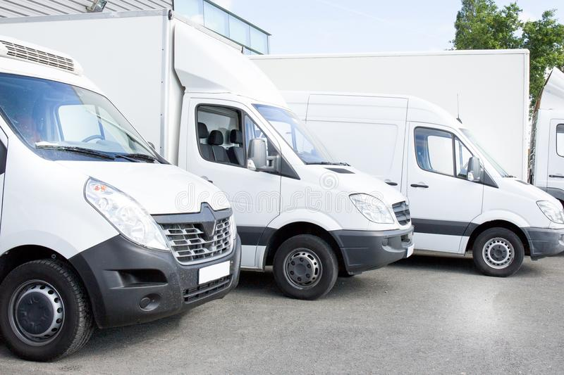 Several white row commercial delivery vans and service van, trucks and car in front of factory warehouse royalty free stock photography