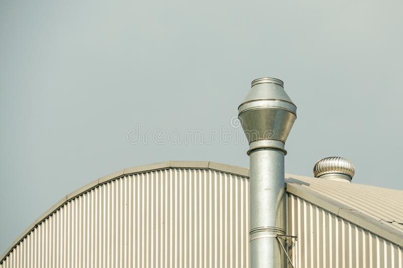 Several white ventilation vents are located near building.  stock image
