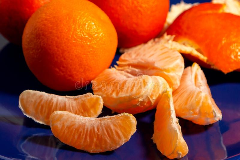 Several whole and peeled ripe tangerines on a blue plate stock photography