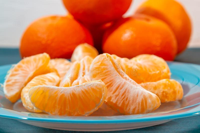 Several whole and peeled ripe tangerines on a turquoise plate royalty free stock image