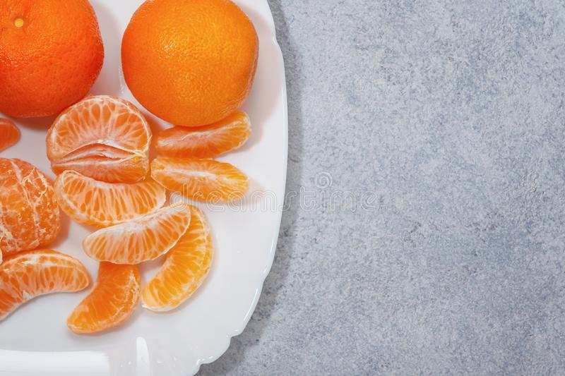 Several whole and peeled ripe tangerines on a white plate on gray background with space for text, flat lay, top view royalty free stock images
