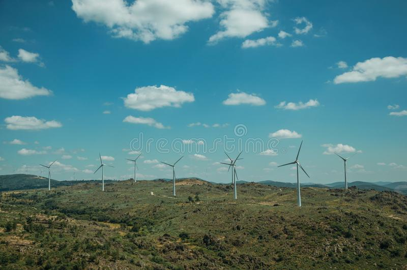 Several wind turbines over hilly landscape. Several wind turbines for electric power generation over green hilly landscape with rocks, in a sunny day at Sortelha royalty free stock images