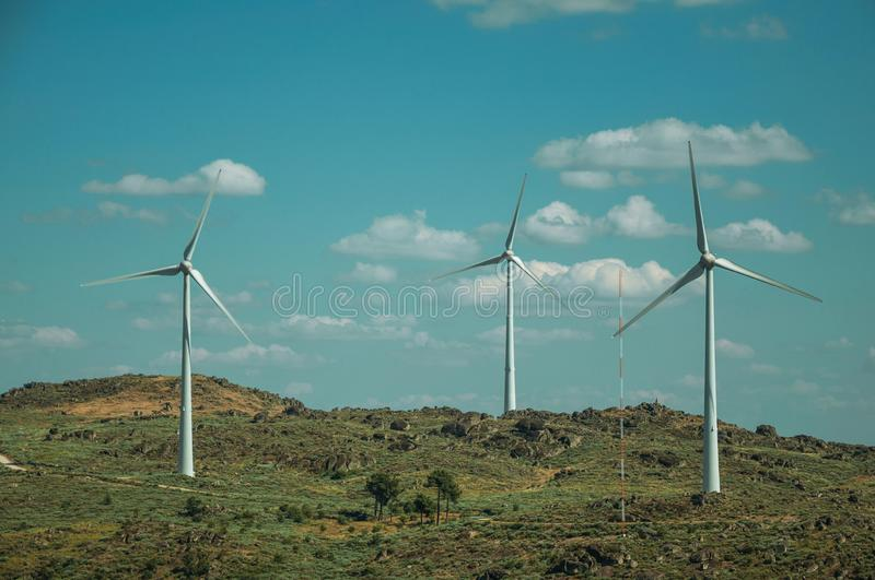 Several wind turbines over hilly landscape. Wind turbines for electric power generation over green hilly landscape with rocks, in a sunny day at Sortelha. One of royalty free stock images