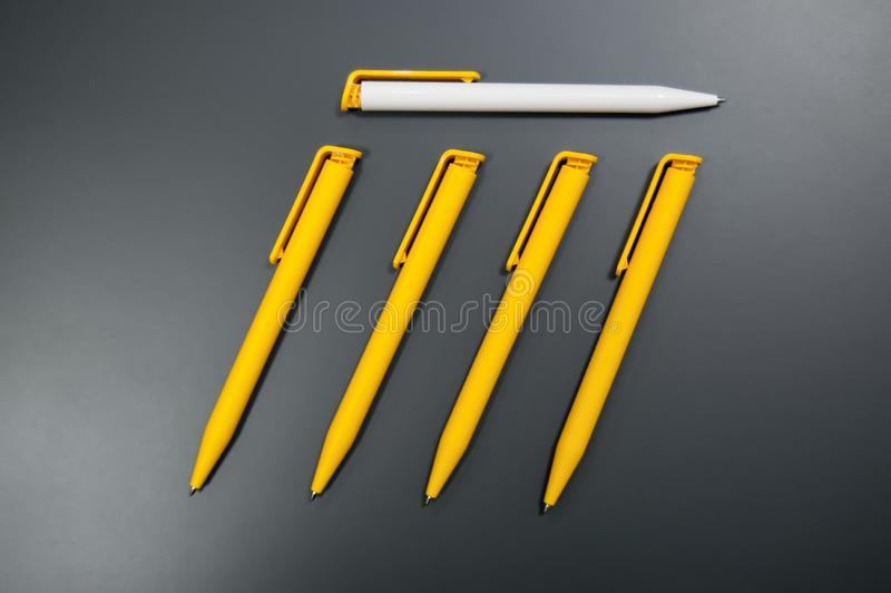 Several yellow and one white plastic pens. leadership concept.  stock images