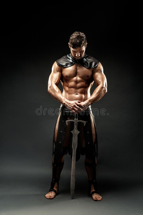 Severe barbarian in leather costume with sword stock photos