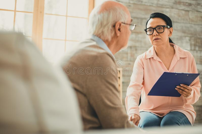 Serious adult woman carrying paper tablet in one hand. Severe facial expression. Serious adult women carrying paper tablet in one hand and calming her patient stock photo