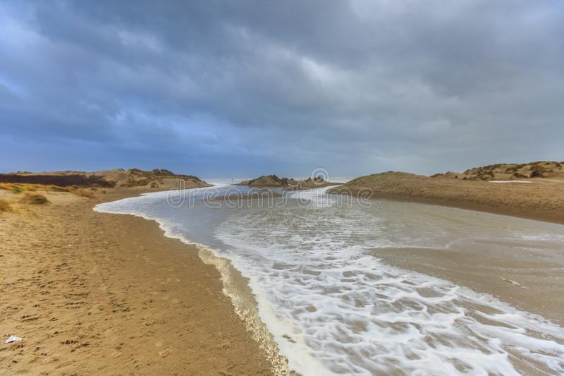 Severe storm along Dutch North Sea coast put Beach to the dunes under water. An opening,  called a slufter, during wester storm in the dunes so that the sea can stock photo