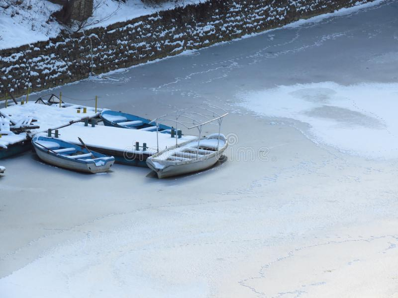 Severe winter. Three small boats frozen in water near by the coast. Frozen river, pond, lake, sea. royalty free stock photos