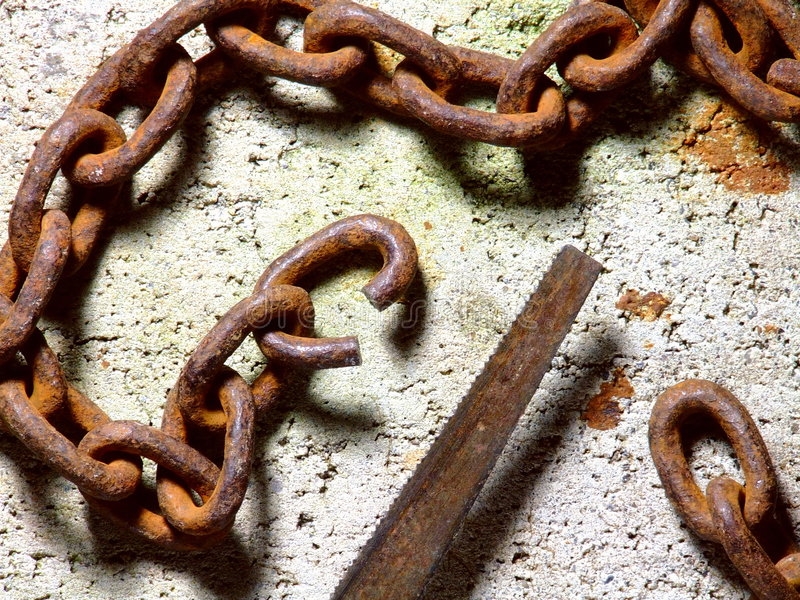 Severed Chain. A length of rusty chain with one link freshly sawed through and opened out so that the chain could be broken royalty free stock photography