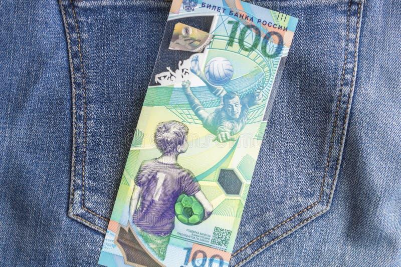 04 21 Severodvinsk 2019 Russland Russische Jubiläumbanknoten von FIFA-Fußballweltcup 2018 100 Rubel auf Jeanshintergrund lizenzfreies stockfoto