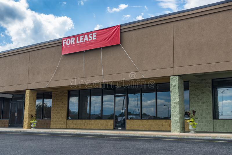 Sevierville, TN / United States - October 15, 2018: Horizontal shot of Retail Space Available in an old strip shopping center. Under a blue cloudy sky. Red For royalty free stock image