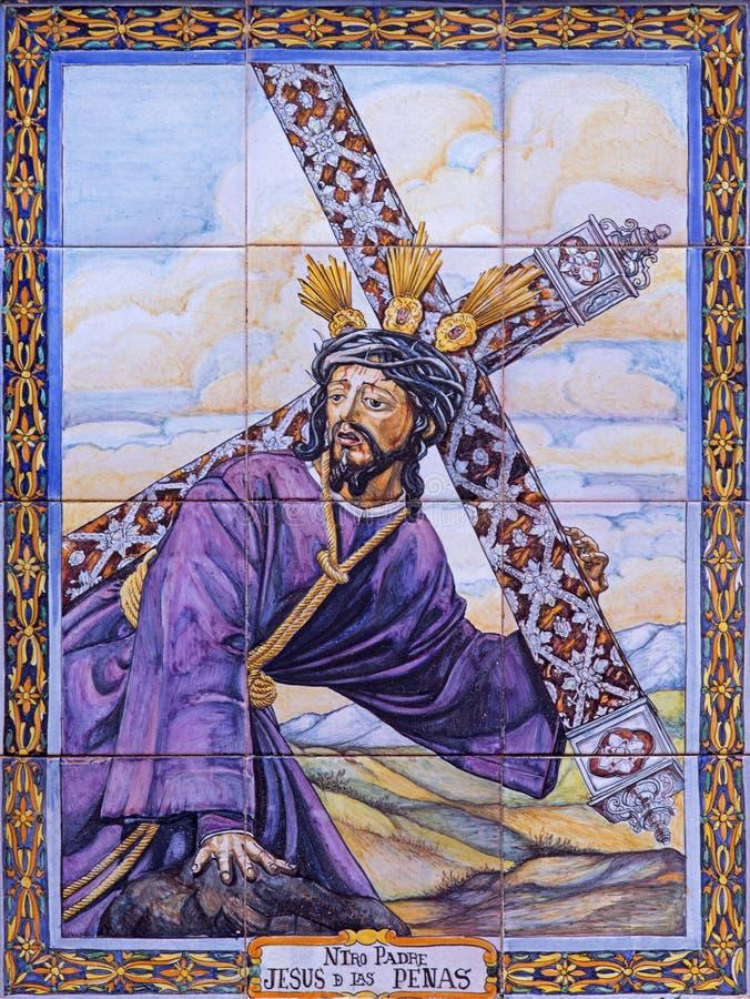 Sevilha - Cristo telhado cerâmico com a cruz por Juan Aragon de 20 centavo na fachada da igreja Iglesia de San Esteban fotografia de stock royalty free