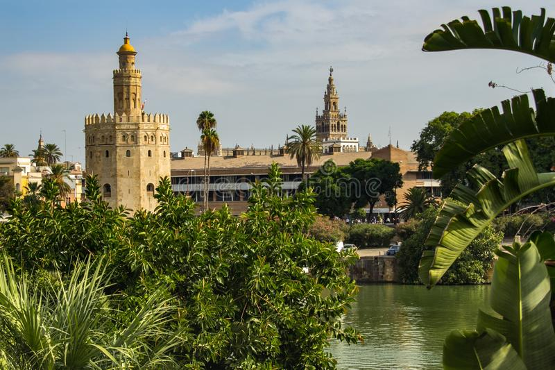Sevilha, Espanha - Sept 23, 2013: Torre del Oro com o La Giralda na distância e o rio no primeiro plano imagem de stock royalty free