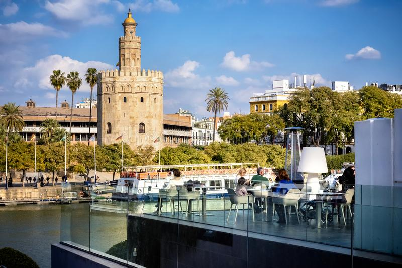 Sevilha: Opinião Torre dourada Torre del Oro de Sevilha com os turistas no restaurante, a Andaluzia, Espanha sobre o rio Guadalqu fotografia de stock