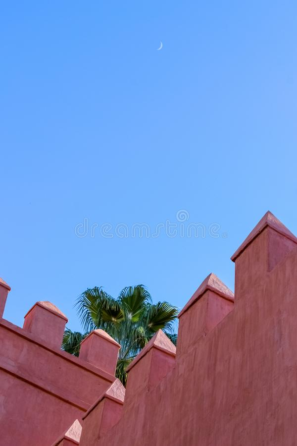 Sevilla Alcazar from the outside: its walls, a palm tree and the moon in a clear blue sky royalty free stock image