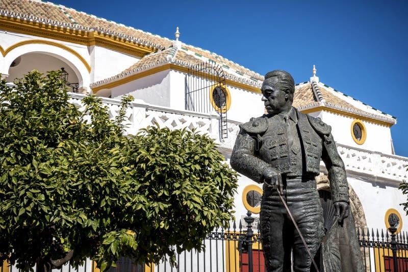 Sevilla, Andalucía, España: La estatua de Curro Romero, torero famoso de Sevilla, delante del la Maestranza de Plaza de Toros de imagen de archivo libre de regalías