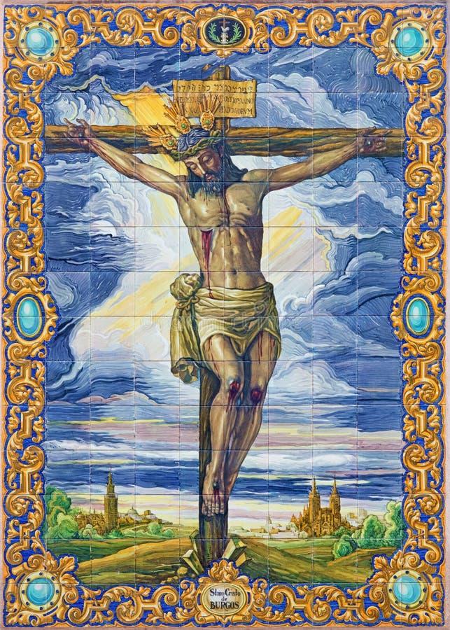 Sevilla - die keramische mit Ziegeln gedeckte Kreuzigung durch Ramos Resano auf der Fassade von Kirche Iglesia De San Pedro stockbilder