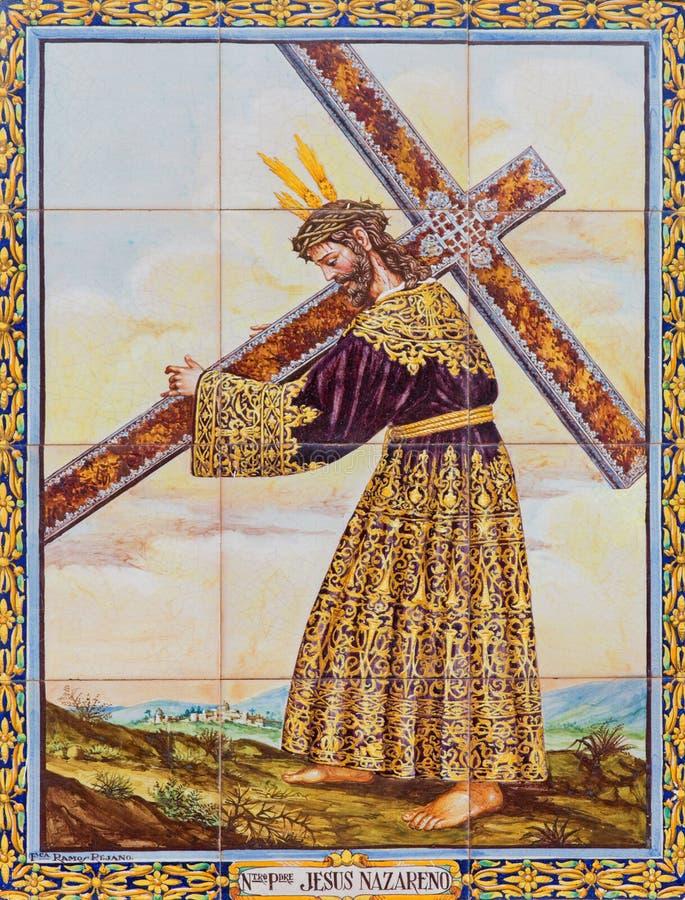 Sevilla - keramischer mit Ziegeln gedeckter Christus mit dem Kreuz durch Künstler A Chaves auf der Fassade von quadratischer Plaz lizenzfreies stockfoto