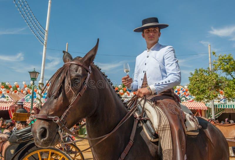 Pferdereiter mit einem Glas von Manzanilla beim des Sevillas April angemessen lizenzfreie stockfotografie