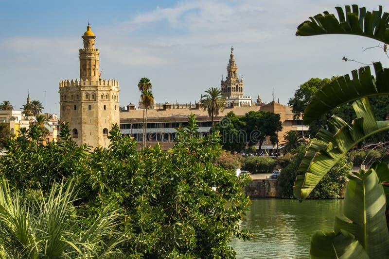 Sevilla, Spanje - Sept. 23, 2013: Torre del Oro met La Giralda in de afstand en de rivier in de voorgrond royalty-vrije stock foto's