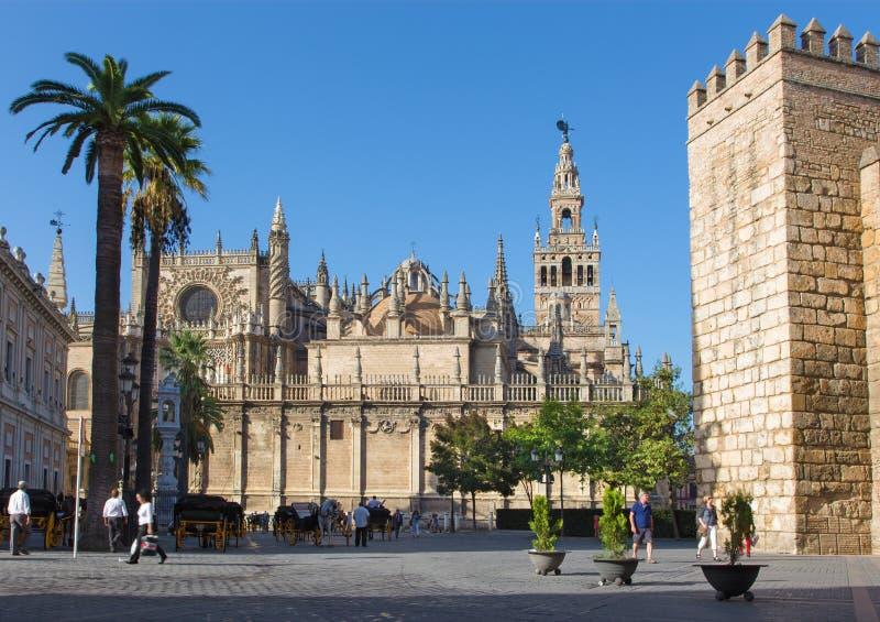 Seville - Cathedral de Santa Maria de la Sede with the Giralda bell tower and walls of Alcazar. stock images
