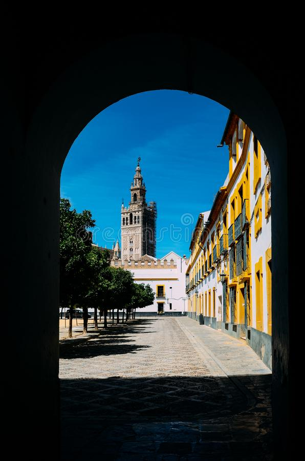 Seville Cathedral`s Moorish Giralda tower as framed from a doorway at courtyard in Real Alcazar, Sevilla, Andalusia stock image