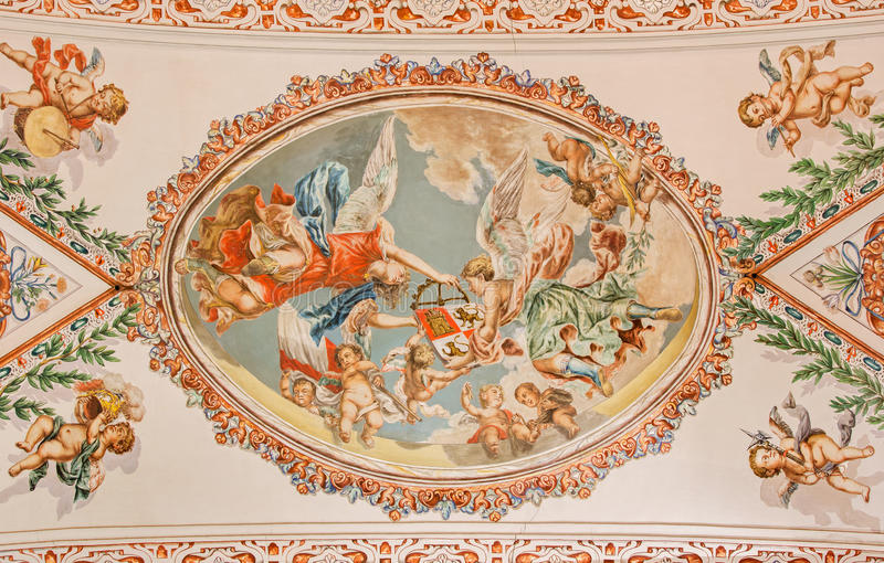 Seville - The fresco of angels with the symbolic crown on the ceiling in church Hospital de los Venerables Sacerdotes. SEVILLE, SPAIN - OCTOBER 28, 2014: The royalty free stock photos