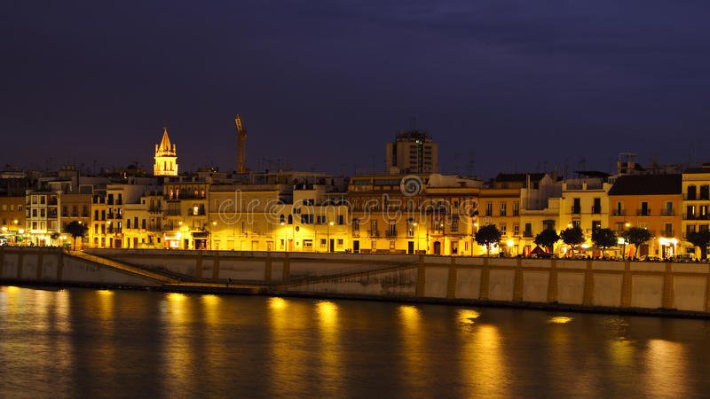 Seville by night. Night view of the buildings reflecting in the waters of Guadalquivir river in Triana district, Seville, Spain. Photo taken on the 26th of stock images