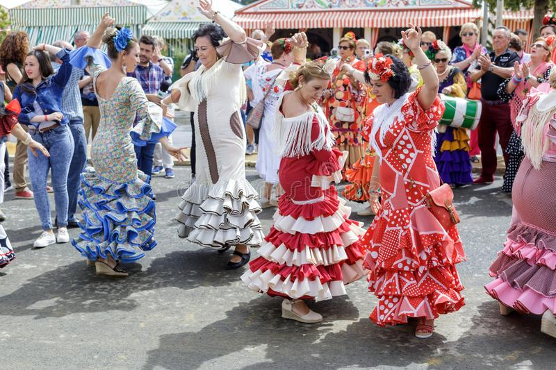 Women wearing traditional Sevillana dresses and dancing a Sevillana at the Seville April Fair. stock images