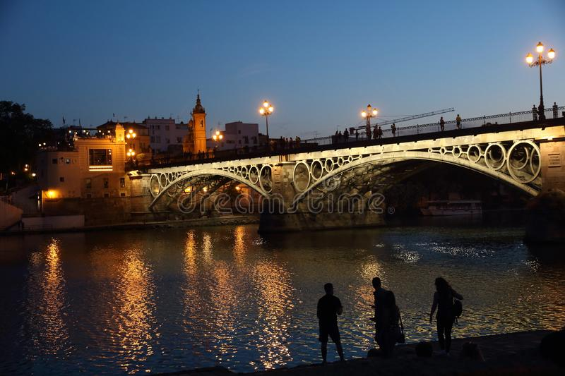 SEVILLE , SPAIN - Mayo 28 2019: Isabel II bridge or Triana bridge. Guadalquivir river. Seville, Andalusia, Spain. Night view of Isabel II bridge over the stock photos