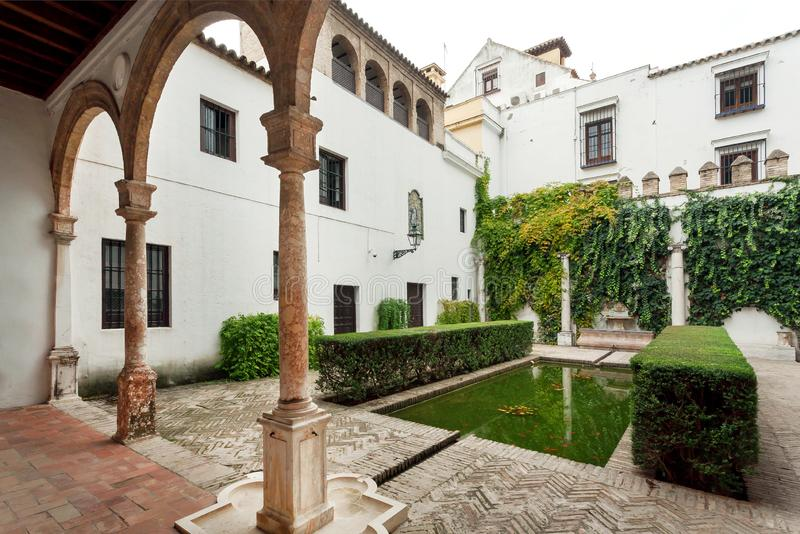 Columns in green courtyard of Alcazar, example of Mudejar architecture of the 14th century, historical royal palace. SEVILLE, SPAIN - NOV 15: Columns in green royalty free stock photos