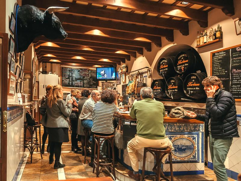 Crowd of people having dinner inside tapas bar with bull head and old wine barrels stock photography