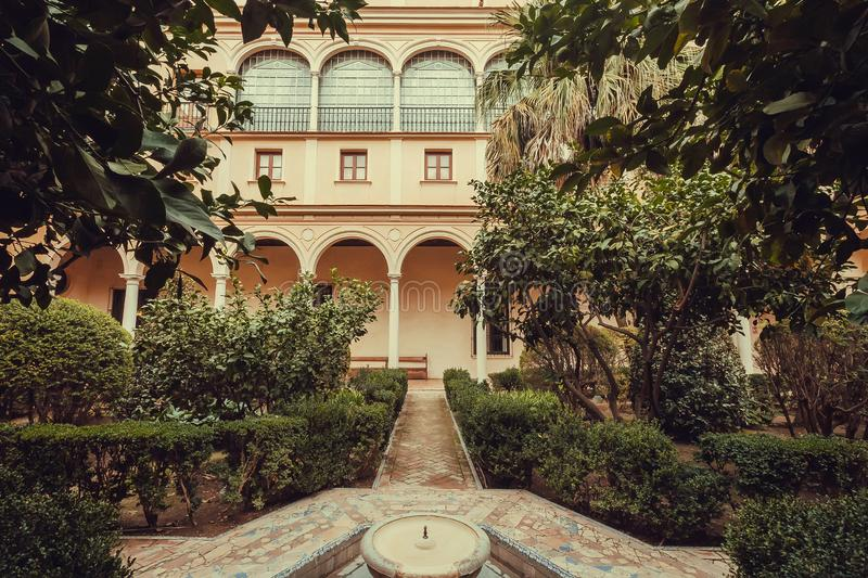 Green courtyard of Alcazar, example of Mudejar architecture of the 14th century, historical royal palace. SEVILLE, SPAIN - NOV 15: Green courtyard of Alcazar stock image