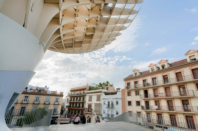 Young people sitting under construction Metropol Parasol, urban project in form of giant mushrooms royalty free stock images