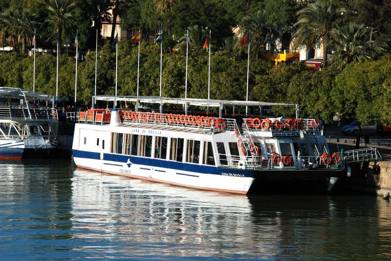 Tour boats moored along the river, Seville, Spain. stock images