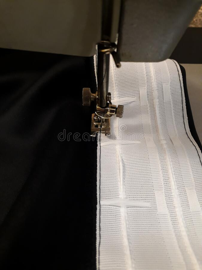 We sew curtains - sewing curtain tape to the fabric. Blackout with your own hands stock images