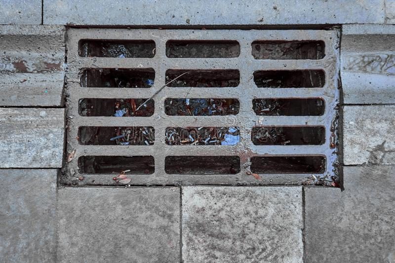 Sewage grate on the road with garbage stock photo