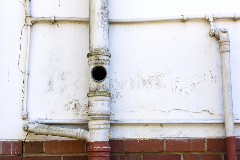 Sewage and Water Pipes on Wall of Residence stock photo