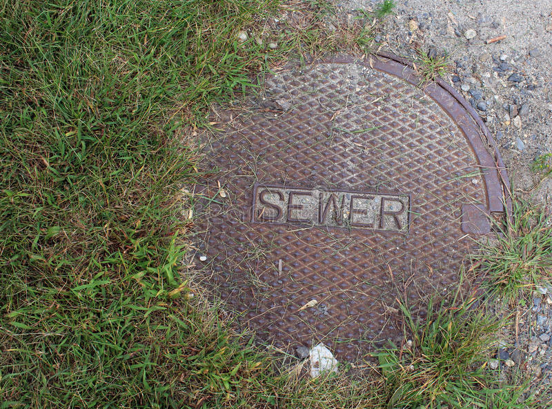 Sewer Cover with Grass and Gravel. Rusted sewer cover diamondplate with green grass and gray gravel stock photos