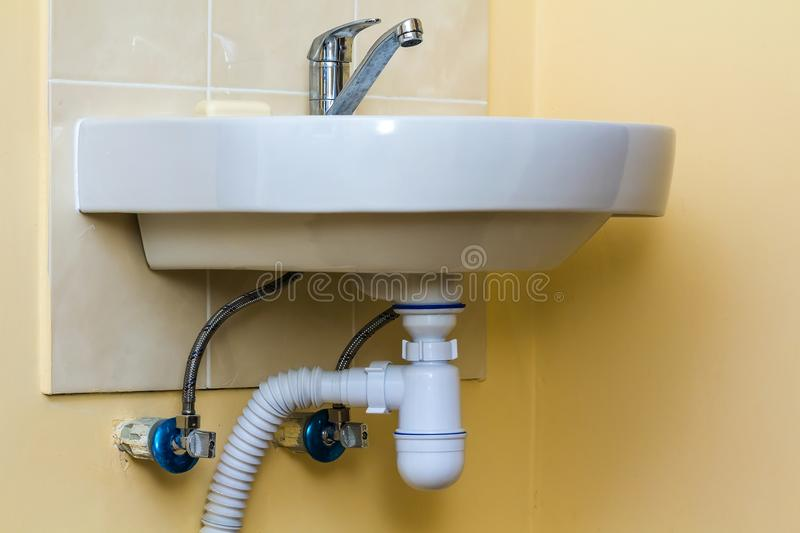 Sewer drain pipes under the kitchen sink. Plumbing fixture and fa. Ucets royalty free stock photo