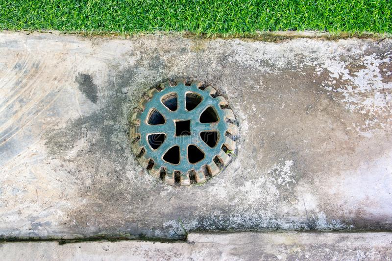 Sewer grate on concrete drain floor. Clogged street drain. Sewer cover. Metal sewer cover. Sewer grate on concrete drain floor. Clogged street drain.S ewer cover royalty free stock photo