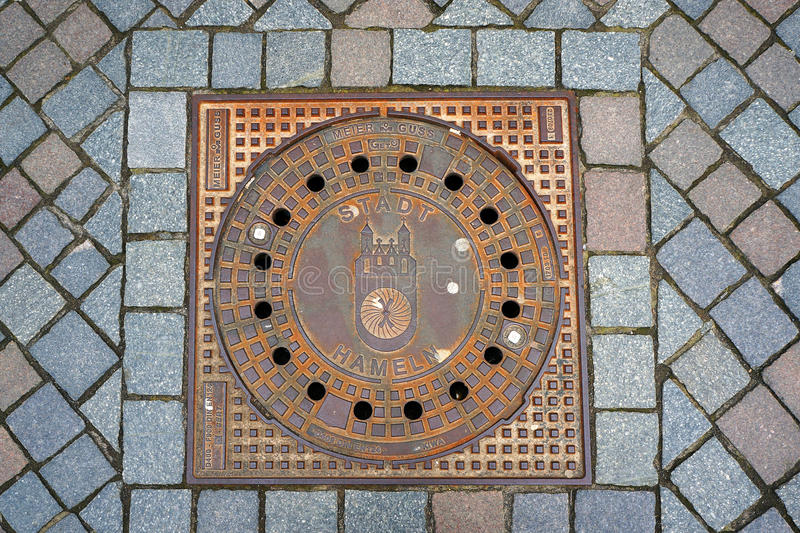 Sewer manhole in city Hameln, Germany. Sewer manhole with emblem of city Hameln, Germany royalty free stock image