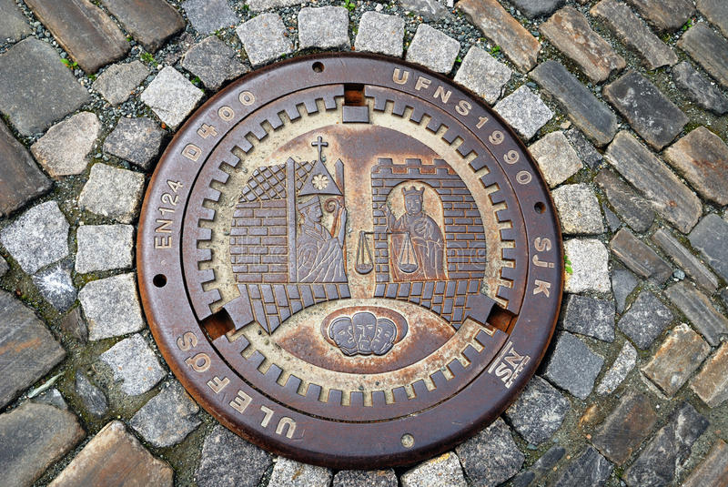 Sewer manhole on the stone pavement. A metal sewer hatch is on the stone block pavement. It is decorated with coining picture of ancient life royalty free stock photos