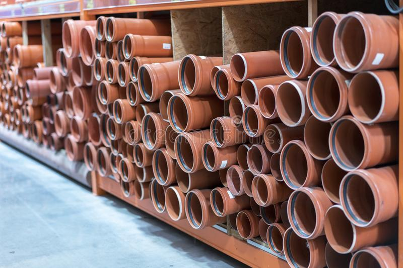 Sewer pipes in the building store. KG sewer pipes. Stacks of PVC and ceramic water pipes stock photography