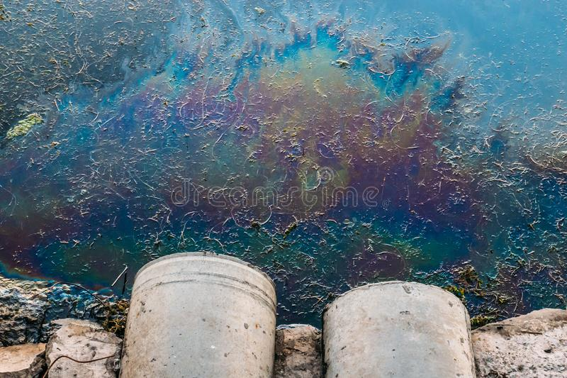 Sewer pipes at shore, stain of oil or fuel on water surface, nature pollution by toxic chemicals, dirty sea royalty free stock photos