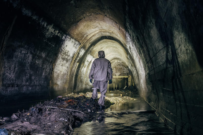Sewer tunnel worker in chemical protective suite in underground gassy sewer tunnel royalty free stock images