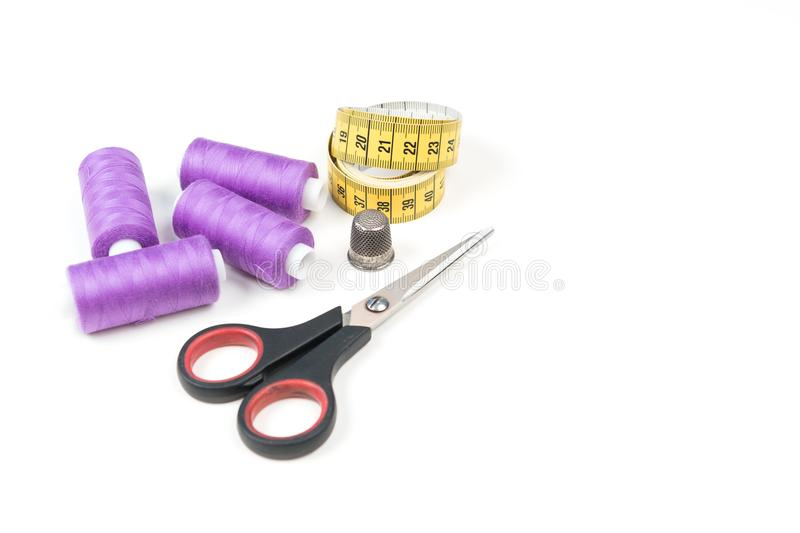 Sewing accessories and tools, orchid purple sewing threads, yellow measuring tape with black numbers, small scissors and metal thi royalty free stock image
