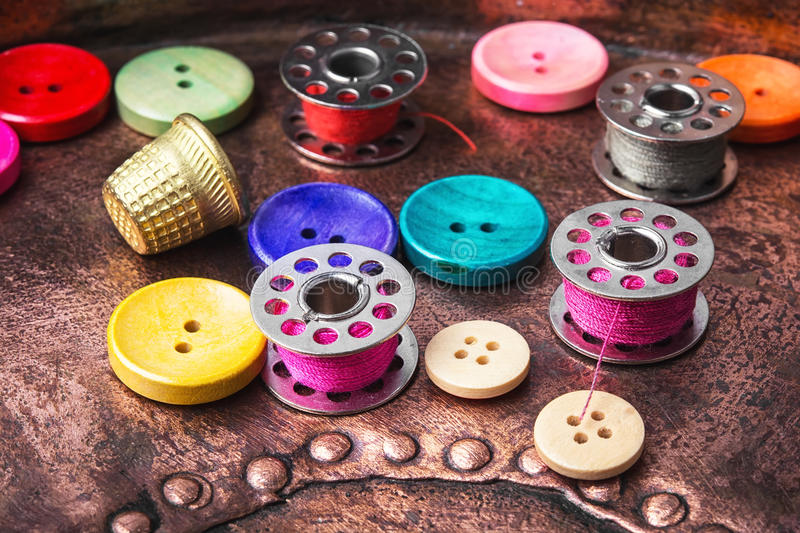Sewing button set. Plastic sewing button and thread coil on a copper retro background royalty free stock photography